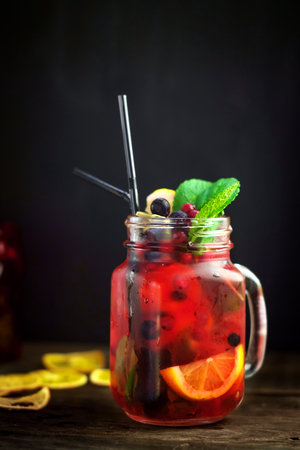 homemade lemonade in glass jar with ice, orange and berries in a tree on a black background Standard-Bild