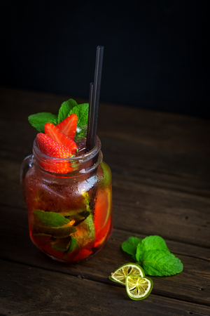 Strawberry Mojito in a glass jar with strawberries on wooden background Stock Photo