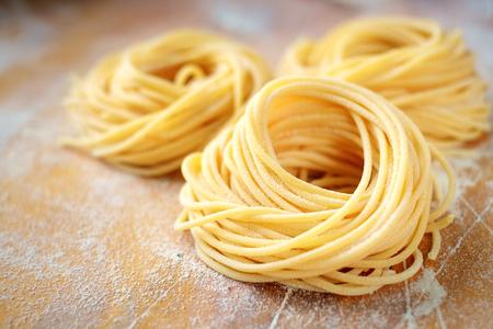 surowe domowe spaghetti gniazdo z mąką na drewnianym stole. świeży włoski makaron