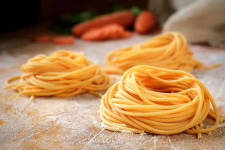 Fresh spaghetti sockets with carrots on the wooden table. Traditional Italian raw pasta 免版税图像