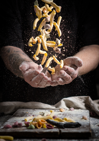 close hand make pasta toss f on a black background before cooking the dish