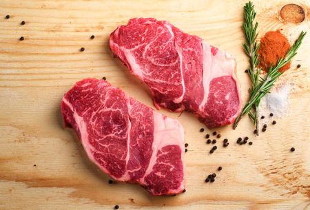 two raw beef neck steak on wooden background with seasonings prepared for cooking