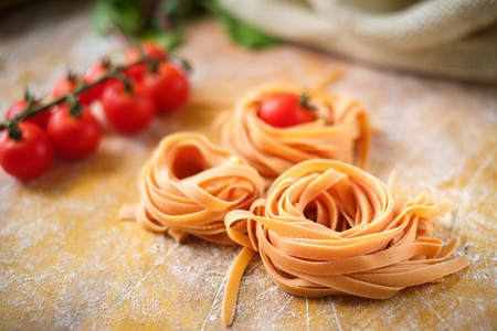homemade tagliatelle nests not cooked on the table with flour and tomatoes Banco de Imagens