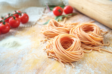 raw homemade colored spaghetti nest with flour on a wooden table. fresh Italian pasta with tomatoes Zdjęcie Seryjne