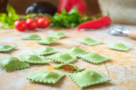 raw green homemade ravioli with spinach and vegetable on wooden table with flour