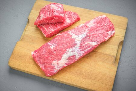 one large piece of beef brisket on a wooden butcher's Board and two small steaks