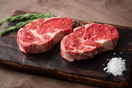 Two fresh raw rib-eye steak on wooden Board on wooden background with salt, pepper and rosemary in a rustic style
