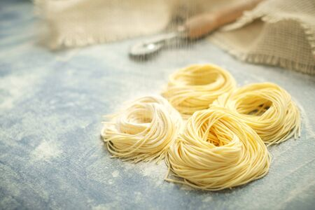 Raw homemade spaghetti nest sprinkle with flour in a kitchen. Cappellini pasta Reklamní fotografie