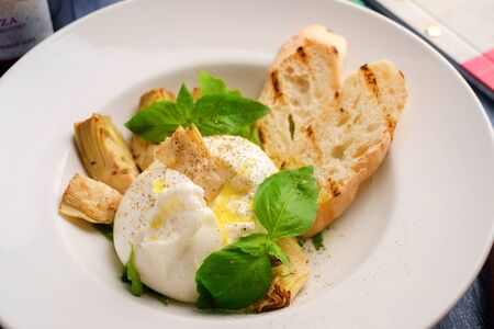 burrata cheese with artichokes and Basil and a white plate on wood table, macro