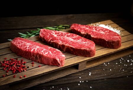raw top blade steak of marbled beef with pepper and salt on wooden background