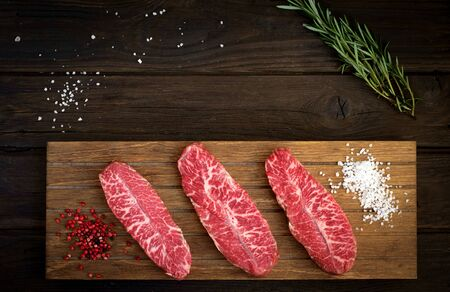 raw top blade steak of marbled beef with pepper and salt on wooden background, top view