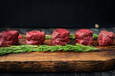 fresh deer fillet cut into pieces lies on a wooden Board with herbs and salt, view from the top