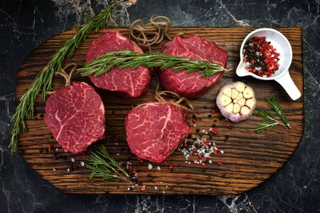 fresh raw fillet minion steaks marbled beef with rosemary and garlic on wooden background, top view