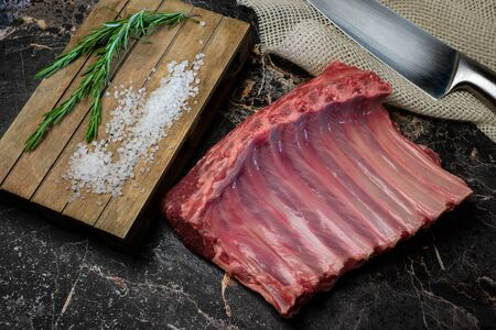 Fresh lamb ribs with rosemary on a dark kitchen table, top view
