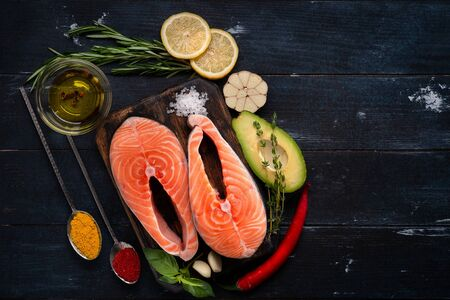 Raw fresh salmon steak with herbs, avocado, basil, lemon and garlic - ingredients for cooking on black wood background, Top view. Healthy food concept Reklamní fotografie