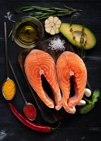 Preparation for cooking two ideal salmon Steaks fish with seasonings and herbs. Healthy proper diet, top view and copy space