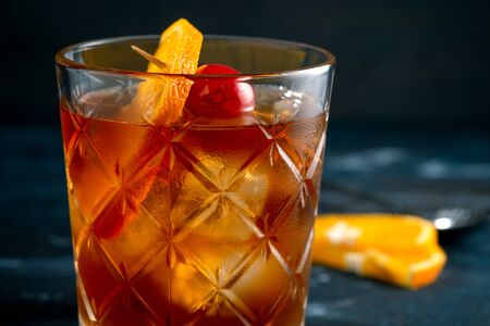 Whiskey sour cocktail with a slice of orange, cherry and ice, a classic alcoholic drink on dark background