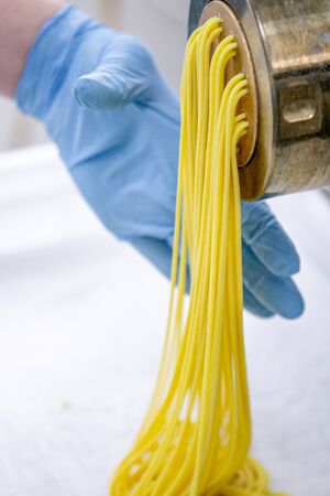 Process of production of pasta. Manufacture of fresh spaghetti with pasta machine Stockfoto
