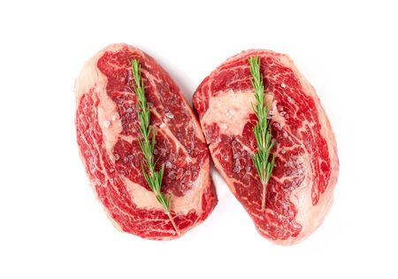 Two raw Rib eye steak marbled beef with salt and rosemary isolated on white background Archivio Fotografico