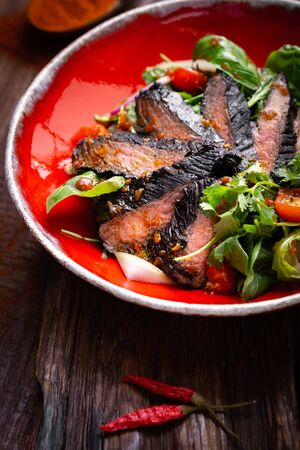Fillet of beef smoked brisket with green salad on wooden table. Roasted Beef cooking idea