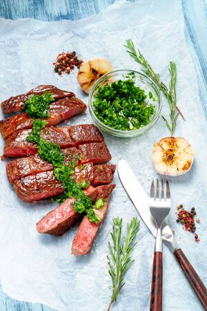 Sliced grilled rib eye beef steak with chimichurri sauce on white paper on wooden background. Concept of cooked steak Foto de archivo