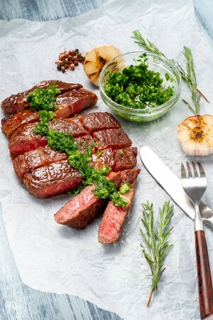 Sliced rib eye beef steak with chimichurri sauce and spices on white paper. Striploin cooked on the grill Foto de archivo