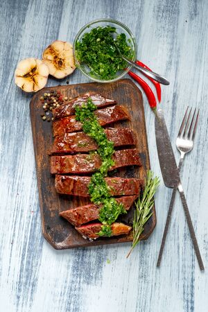 Sliced juicy beef steak with chimichurri sauce and spices on wooden board. Foto de archivo