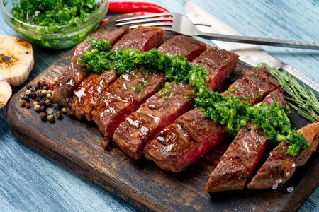 Sliced juicy beef steak with chimichurri sauce and spices on wooden board.