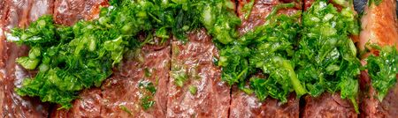 Roast sliced beef Steak medium rare Striploin with chimichurri sauce close up Foto de archivo