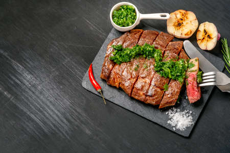 Ready to eat black Angus beef rib eye steak sliced with herbs, garlic and sauce on slate Board. Ready meal for dinner on black wooden background