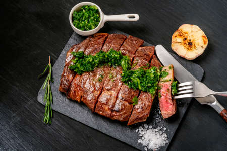 Ready to eat black Angus beef rib eye steak sliced with herbs, garlic and sauce on slate Board. Ready meal for dinner on the background of dark ebony. Archivio Fotografico