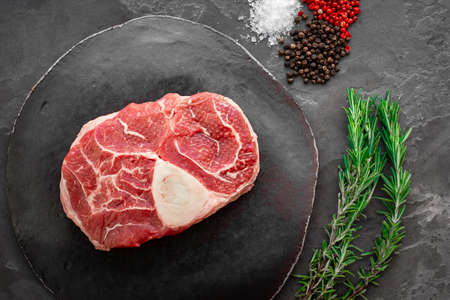 Raw beef meat osso buco steak on round slate cutting board. Top view 스톡 콘텐츠