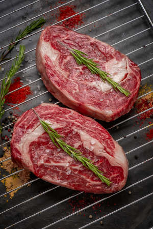 Two juicy raw rib eye steaks prepared for grilling with spices and herbs. Reklamní fotografie