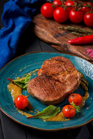 Large grilled beef steak on a plate with cherry tomatoes and mustard in plate on wooden dark background Reklamní fotografie