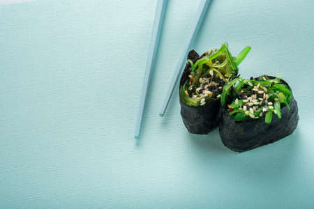 Two Chuka seaweed Sushi with chopsticks on a blue background Stock Photo