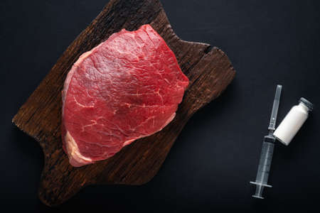 Injection of antibiotic into raw meat. Chemical experiments in food production.