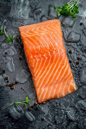 Fresh natural raw salmon fillet on ice cut into steak on a stone background with seasonings and herbs, top view