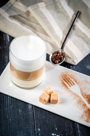 Glass Cup of coffee latte with foam on a blue wooden table with sugar and a napkin