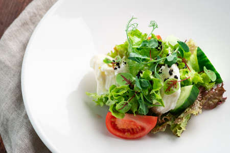 Light diet salad of mozzarella and fresh vegetables -cucumber, tomato, lettuce, peas on a white plate on a wooden background