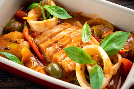 Cod stewed with vegetables and Basil in tomato sauce in a deep dish, close up