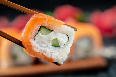 Philadelphia sushi roll in chopsticks on the background of a set of Japanese food, close-up