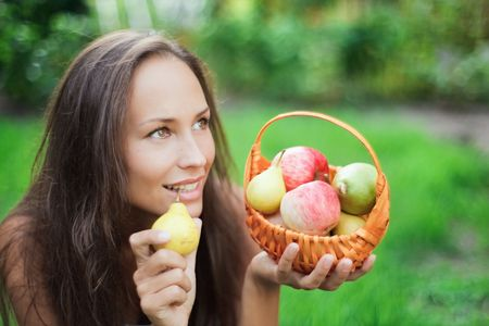 Beautiful girl outdoor with apples and pears in the crib photo