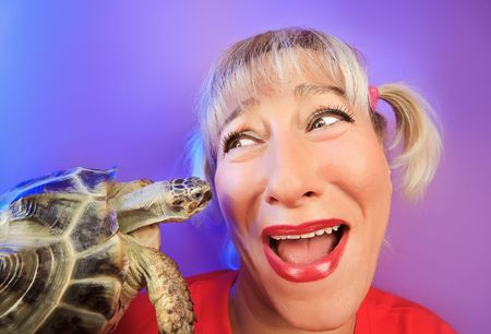 Funny woman with tortoise on vivid color background photo