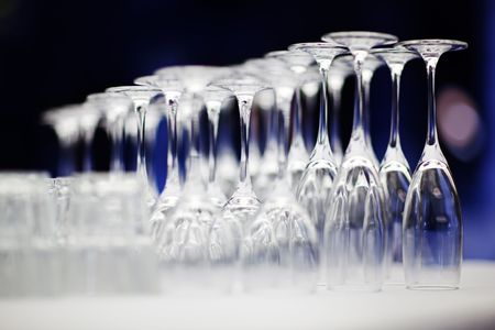 upturned: Upturned set of wine glasses on blurred blue background with extremely shallow depth of field. Stock Photo