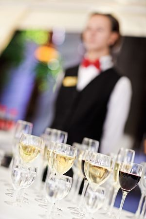 Set of wine glasses with waiter on blurred background. Shallow depth of field. photo