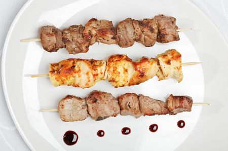Chicken,  pork and veal kebab on white plate with sauce photo