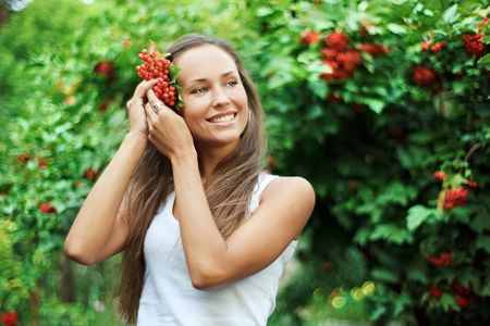 Beautiful woman with guelder rose in hair photo