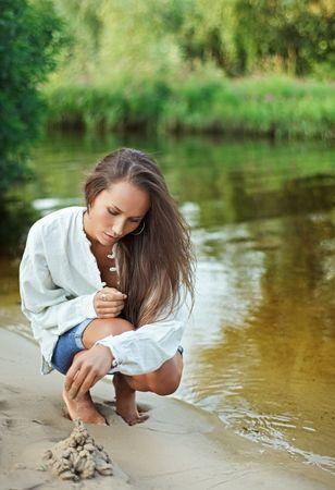 bilding: Beautiful young woman bilding sand castle