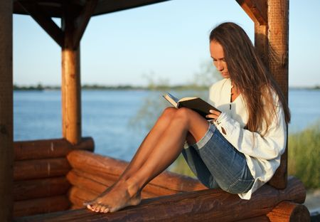 log book: Young woman reading book in summerhouse on sunset Stock Photo