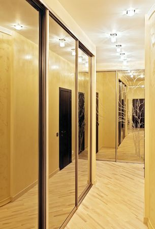 closet door: Passage with a mirror wardrobe in warm tones
